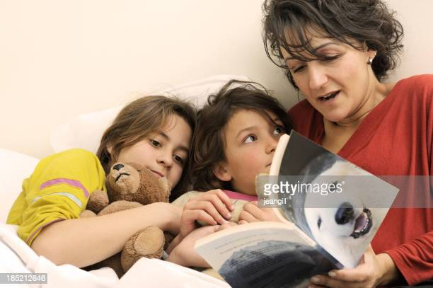 Mother reading bedtime story to daughters