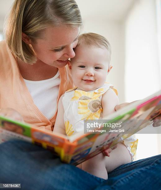 Mother reading book to her baby daughter
