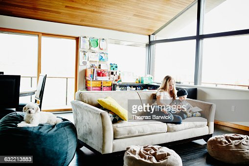 Mother reading book with son on couch