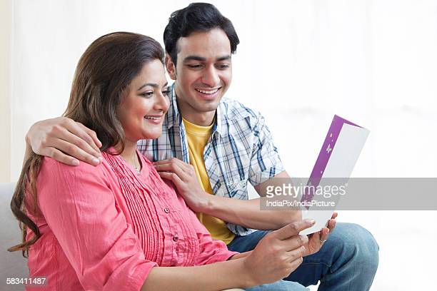 Mother reading card with son