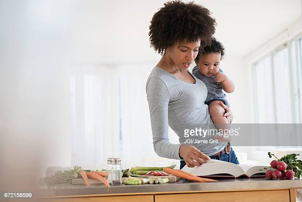 Mother reading cookbook while holding baby son