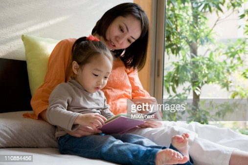 Mother Reading Picture Book for Daughter : Stock-Foto