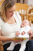 Mother Reading Story To Baby In Nursery