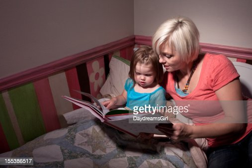 Mother Reading Story to Child in Bed