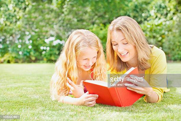Mother reading to daughter in backyard