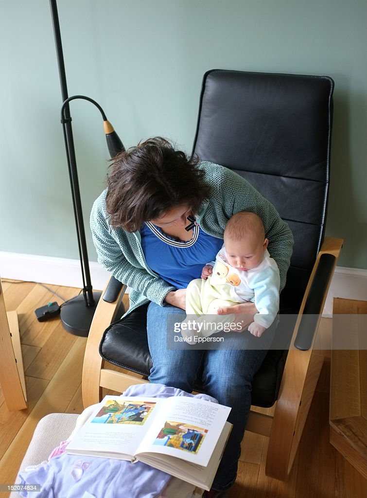 Mother reading to infant daughter : Stock Photo