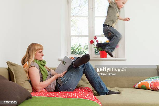 Mother relaxing as son jumps on sofa