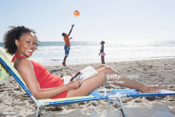 Mother relaxing while children as on beach