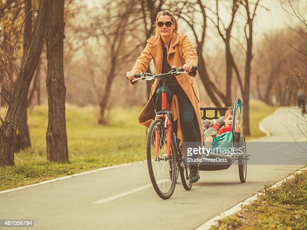 Mother riding a bicycle with kids on trailer