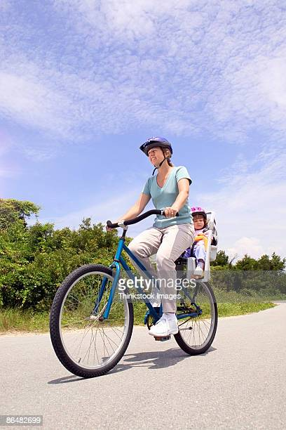 Mother riding bicycle with daughter