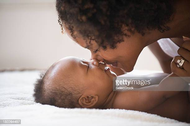 Mother rubbing nose with baby boy