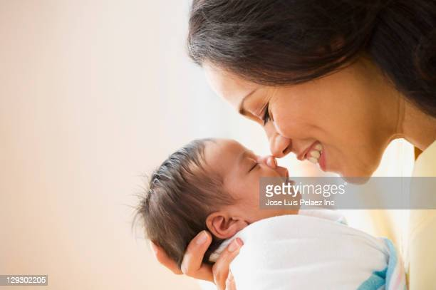 Mother rubbing noses with newborn baby girl