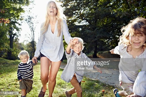 mother running in a park with her children : Stock Photo