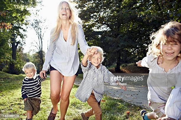 mother running in a park with her children