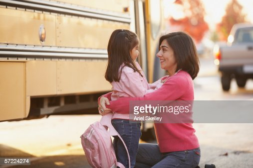 Mother saying goodbye to daughter at school bus