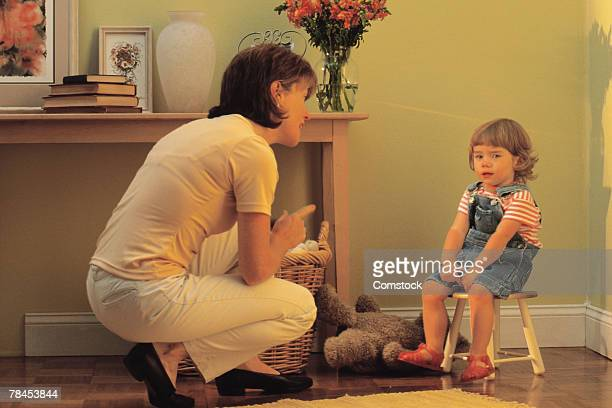 Mother scolding child sitting on stool in corner