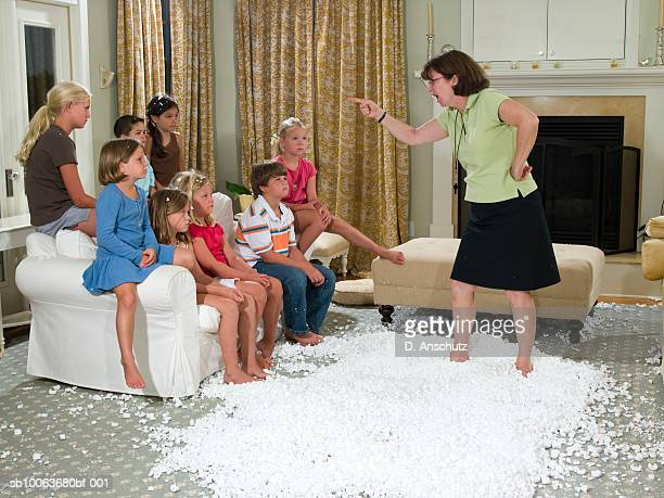 Mother scolding children (3-11), standing in pile of packing peanut in living room