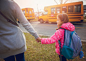 Mother Seeing Her Daughter Off to School. Waiting for school bus to pick her up, holding hands.