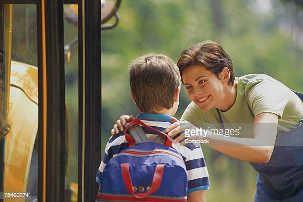 Mother seeing son off at bus stop