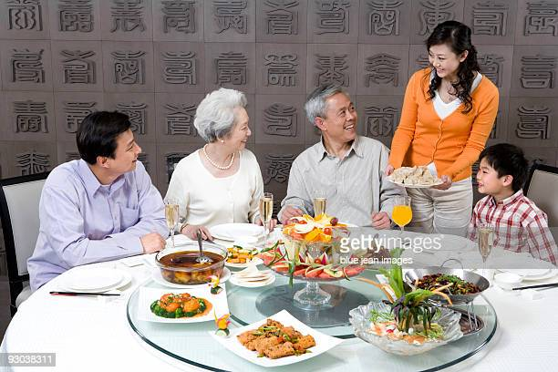 Mother serves dumplings to Grandparents, Husband and Son