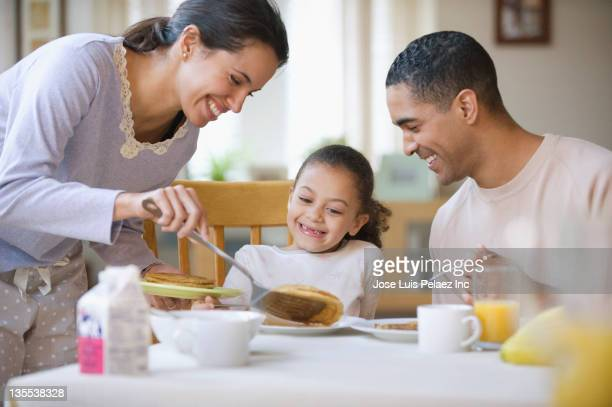 Mother serving daughter pancakes for breakfast