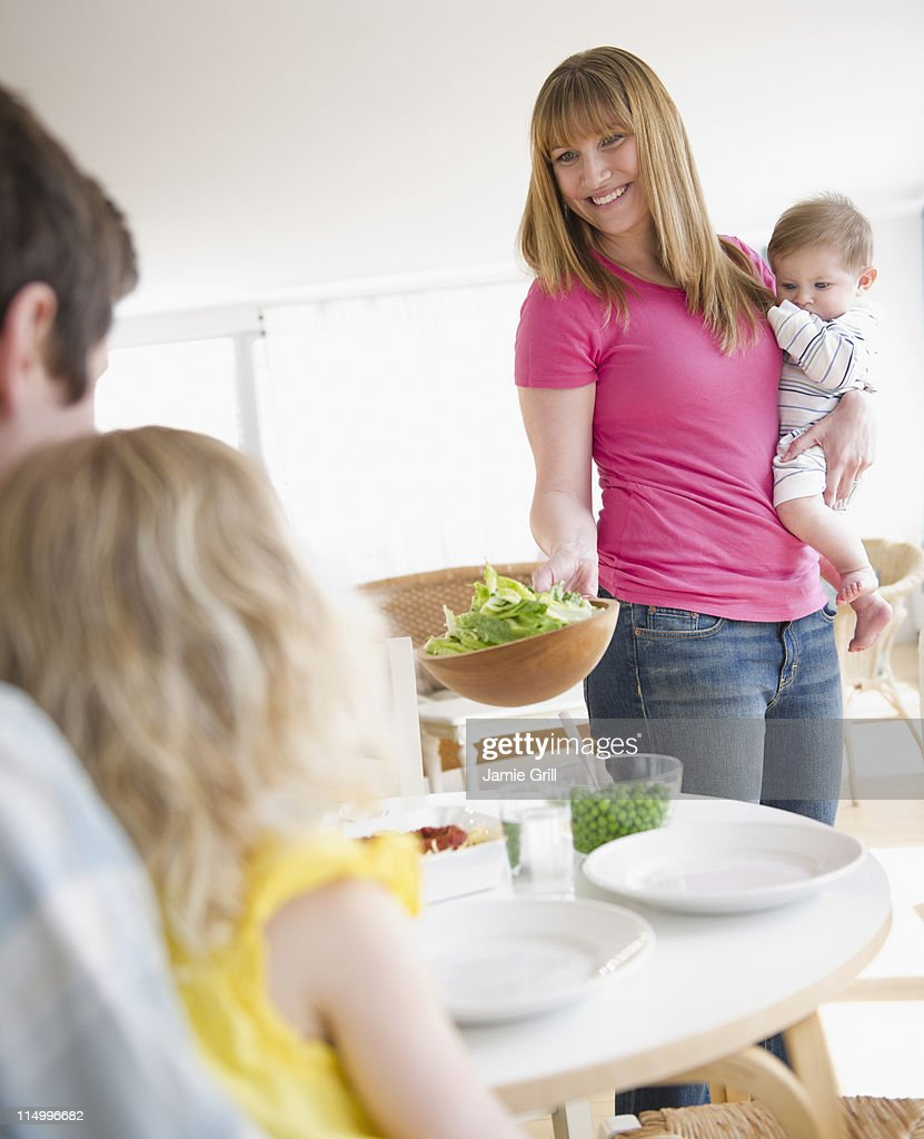 Mother serving dinner while holding baby : Stock Photo