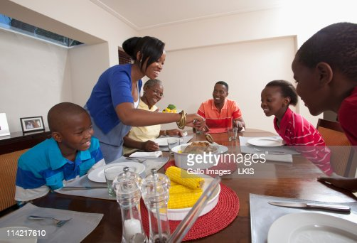 Mother Serving Food At Dining Room Table Johannesburg South Africa Stock Photo