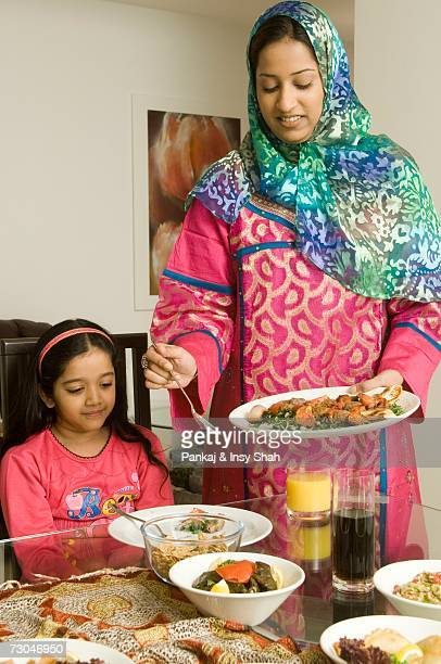 Mother serving food to daughter