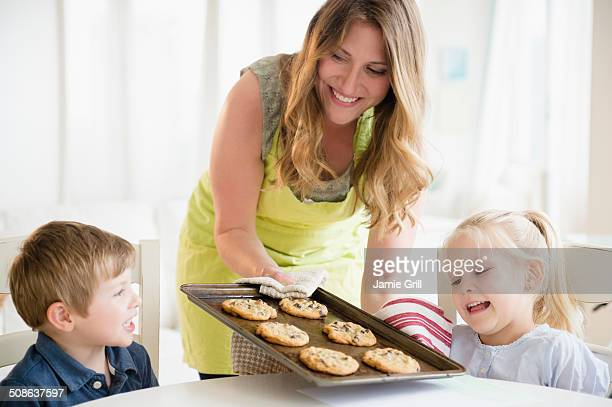 Mother serving freshly baked cookies to kids