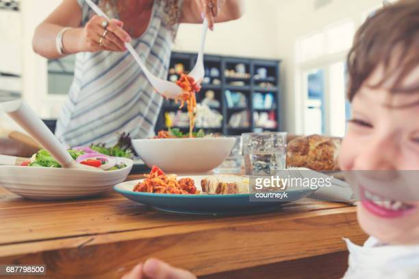 Mother serving her son spaghetti.