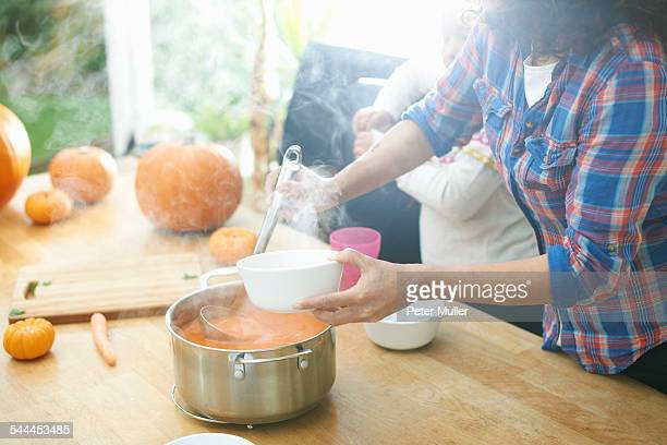Mother serving pumpkin soup for daughter in kitchen