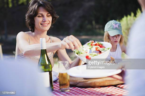 Mother serving salad at picnic