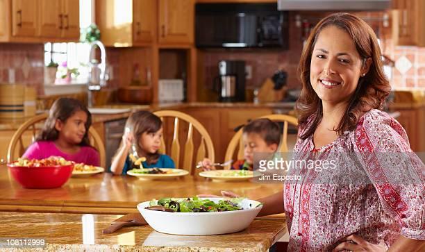 Mother serving salad to children