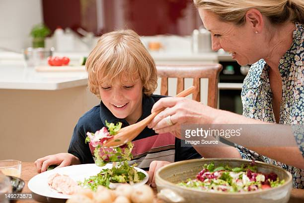 Mother serving salad to son at dining table