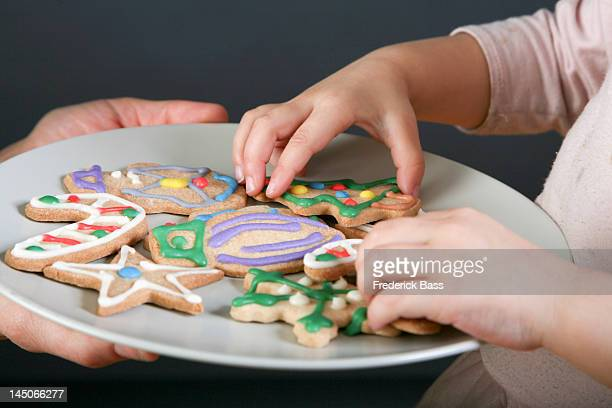 A mother sharing a plate of Christmas cookies with her daughter, focus on hands