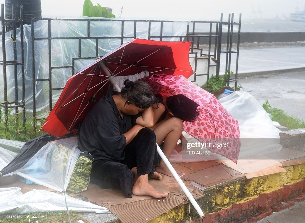 A mother shelters with her son from the wind and rain brought on by typhoon Koppu along Roxas boulevard in Manila on October 18 as the typhoon hit...