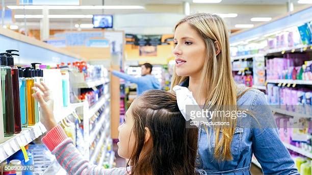 Mother shopping for beauty products in supermarket with daughter