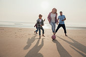Mother showing off her football tricks while playing football at the beach with her family.