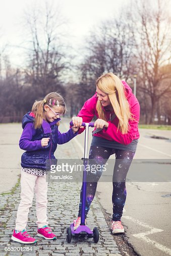 Mother showing her daughter how to ride on a push scooter : Stock-Foto