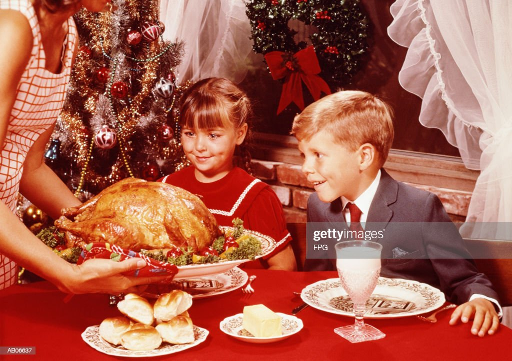 Mother showing roast turkey to children (7-10) at Christmas meal : Stock Photo