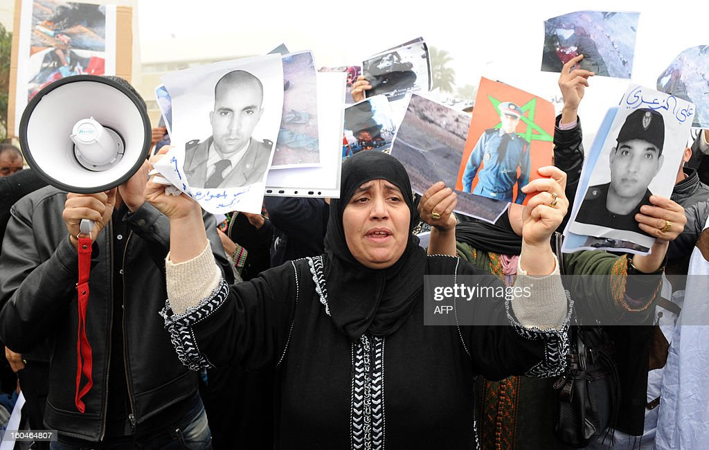 A mother shows pictures of her son who was killed in 2010 after clashes between security forces and Sahrawis, during a demonstration in front of the court in Rabat, on February 1, 2013. Rival protests were held outside a military tribunal in the Moroccan capital where 24 Sahrawis accused of killing members of the security forces in the Western Sahara in 2010 are being tried.