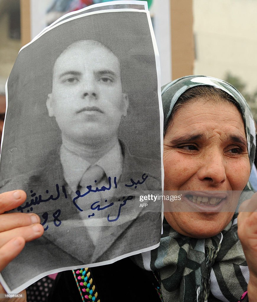 A mother shows pictures of her son who was killed in 2010 after clashes between security forces and Sahrawis, during a demonstration in front of the court in Rabat, on February 1, 2013. Rival protests were held outside a military tribunal in the Moroccan capital where 24 Sahrawis accused of killing members of the security forces in the Western Sahara in 2010 are being tried. AFP PHOTO/FADEL SENNA