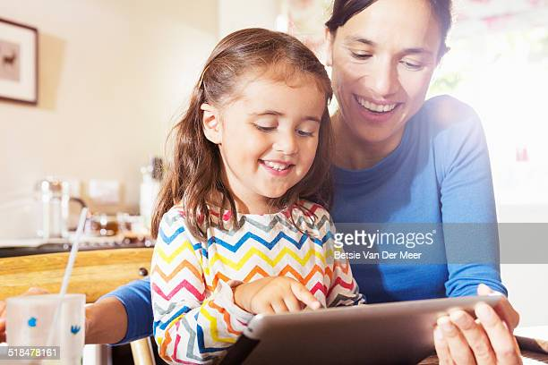mother shows young child to use digital tablet
