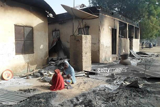 TOPSHOT A mother sits mourning the death of her husband after Boko Haram attacks at Dalori village on the outskirts of Maiduguri in northeastern...