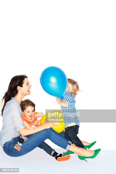 mother sits with her children playing with balloons