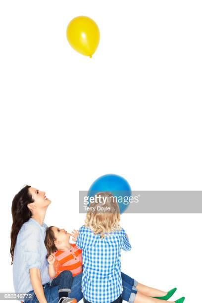 mother sits with her children watching a balloon float away
