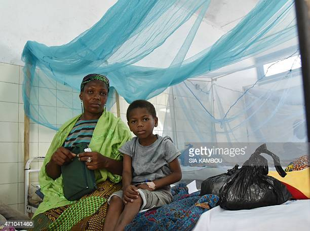 A mother sits with her sick child in a bed with mosquito net in a hospital on April 24 2015 in the popular suburb of PortBouet in Abidjan on the eve...