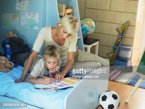 mother sitting by son in bedroom stock photo getty images