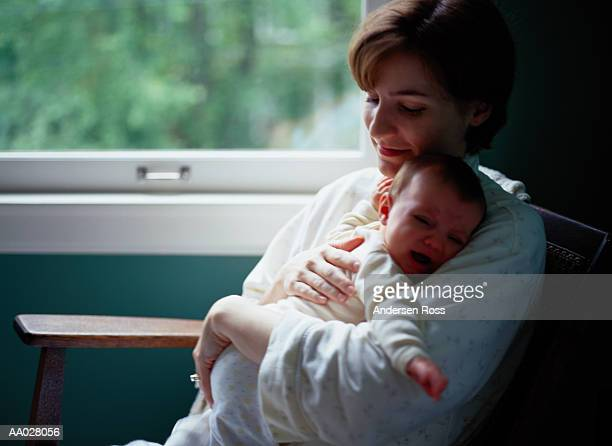 Mother sitting in rocking chair holding baby girl (6-9 months)