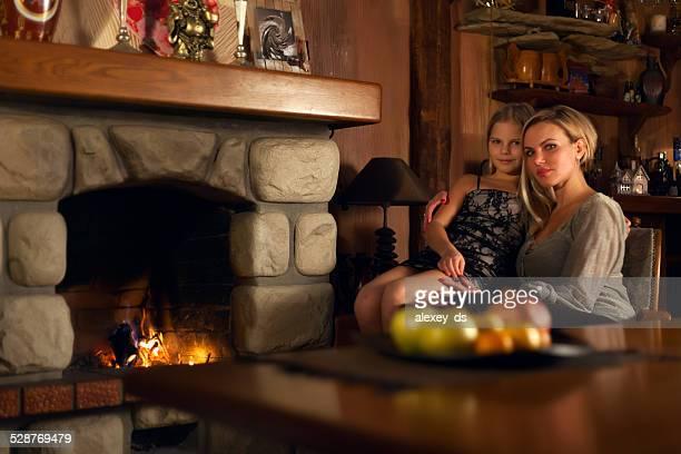 Mère assise près de la cheminée avec sa petite fille